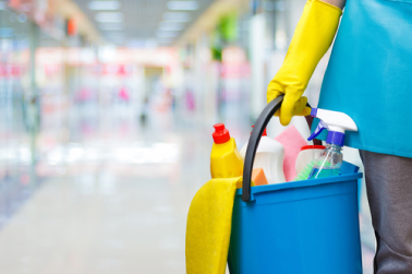 sanitary worker carrying cleaning supplies in a bucket