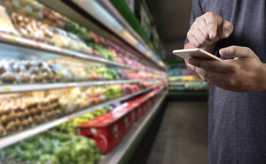 man holding a mobile device in the vegetable isle of a grocery illustrating one of the four food trends in 2018 that grocery retailers should know.