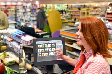 cashier working a POS touch screen while checking someone out in her register lane