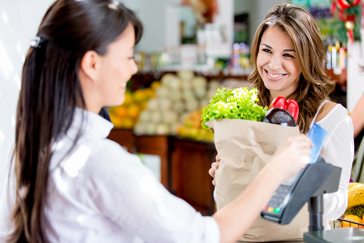 A female cashier using retail technology to help  a customer with her health and natural food purchases as she stands at the checkout.