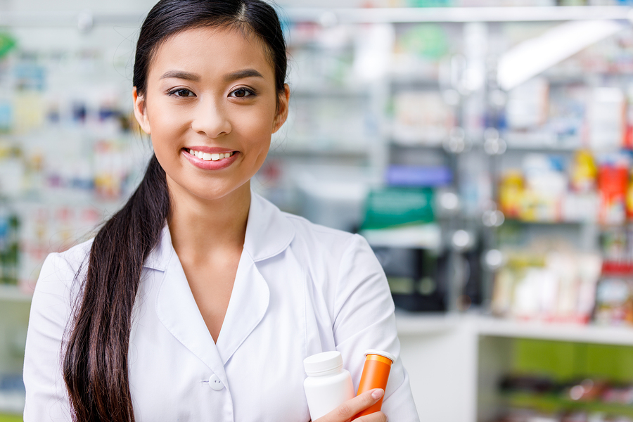 A pharmacist inside a retail pharmacy standing with her arms crossed looking at viewer