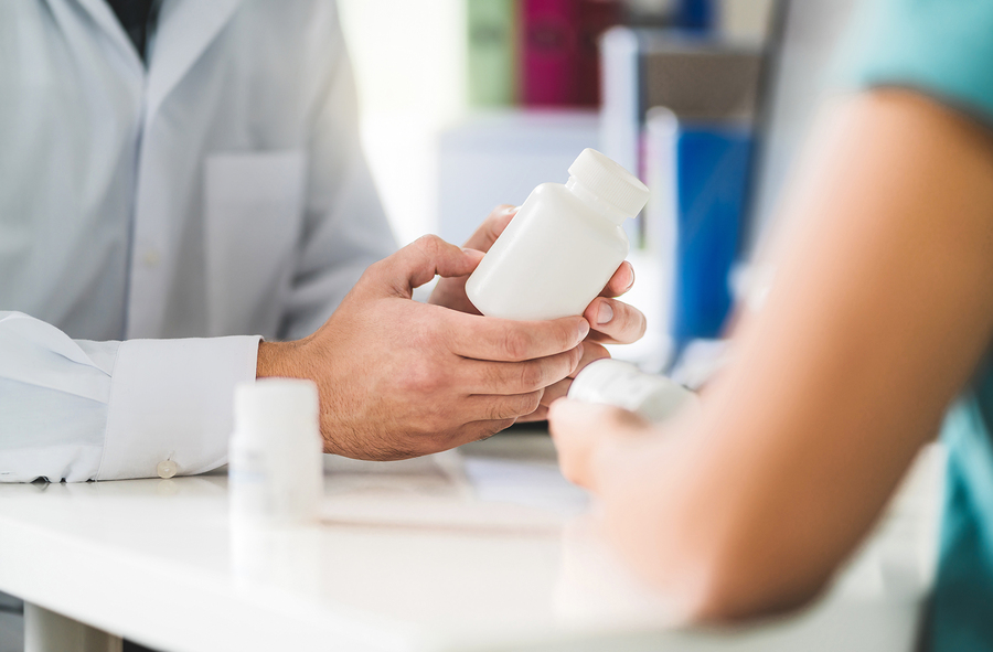 Doctor consulting patient about right medication. Physician holding medicine and pills in hand. Pharmacist in pharmacy in customer service.