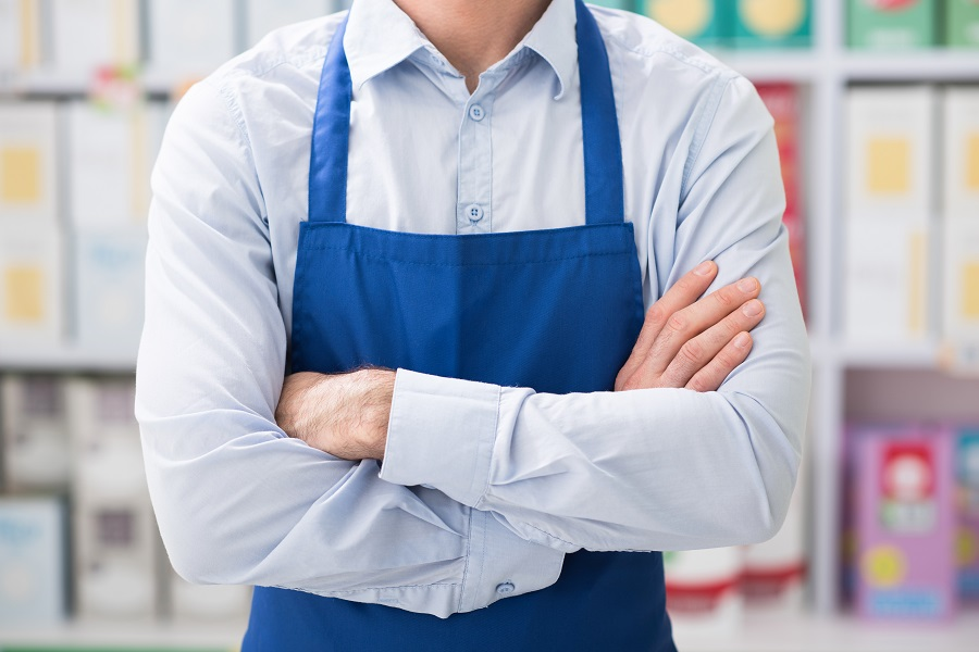 grocery store owner standing in front of the product shelves with his arms crossed
