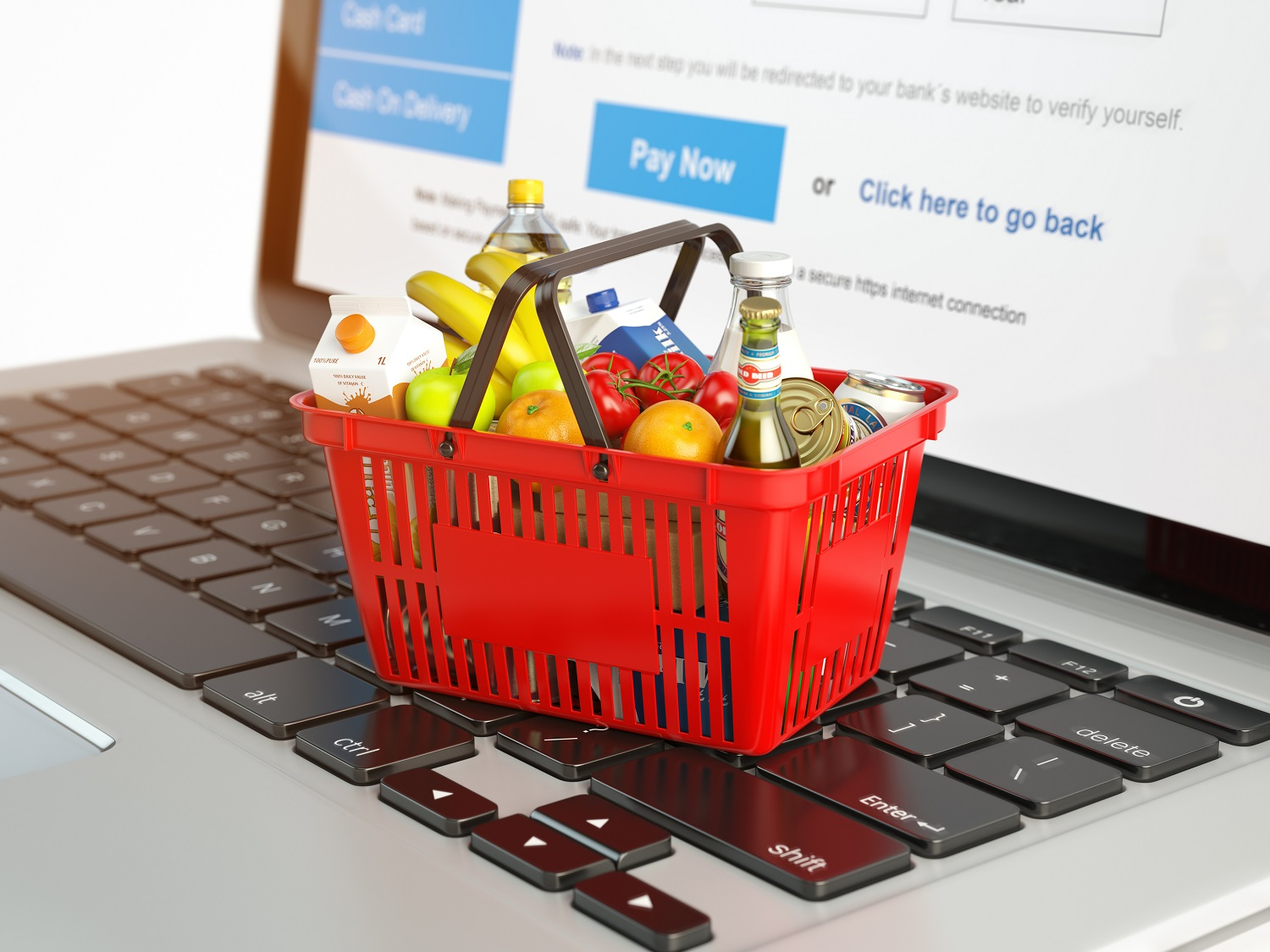 red grocery store shopping basket filled with grocery items sitting on top of a laptop keyboard to illustrate ecommerce concept for the grocery industry