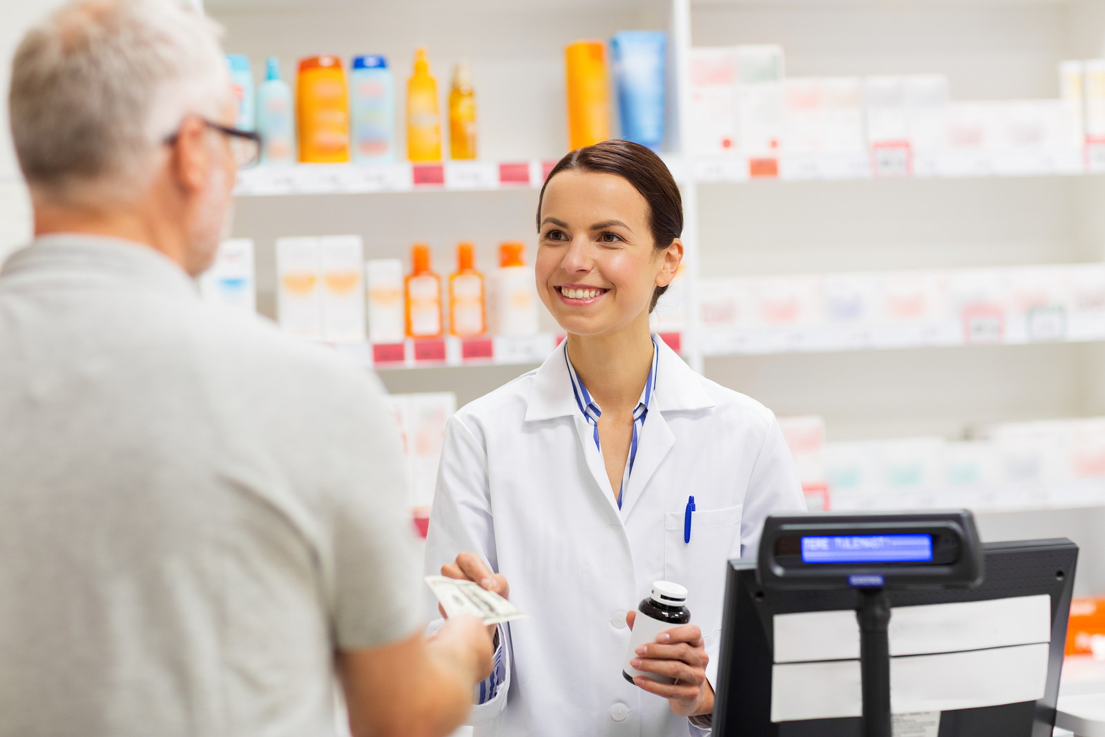 female pharmacist smiling and collecting payment from happy pharmacy customer at the checkout point of sale counter