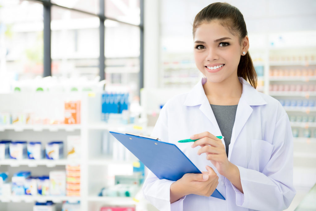 Smiling Asian female pharmacist working in chemist shop or pharmacy