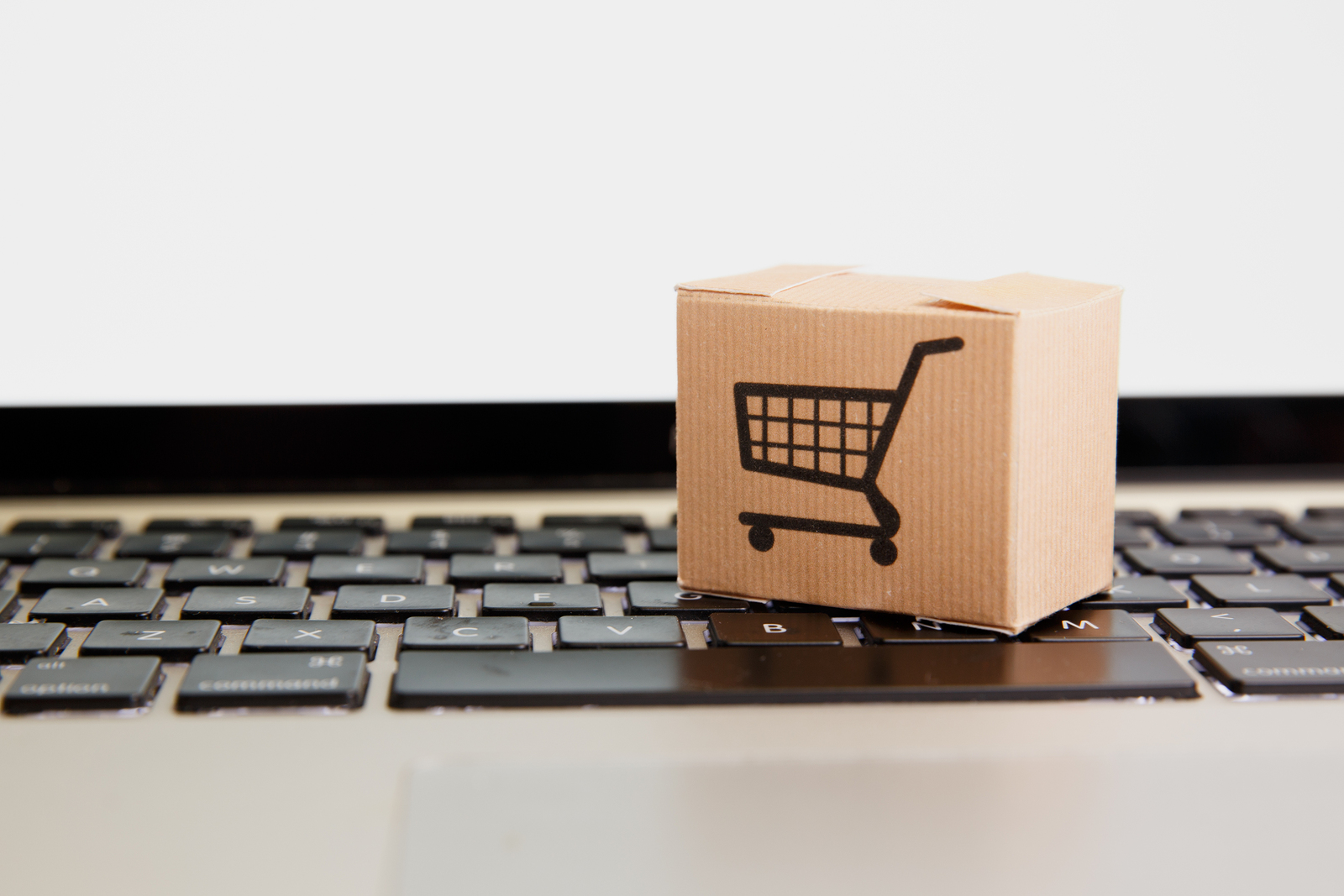 Online shopping . ecommerce and delivery service concept : Paper cartons with a cart or trolley logo on a laptop keyboard, depicts customers order things from retailer sites
