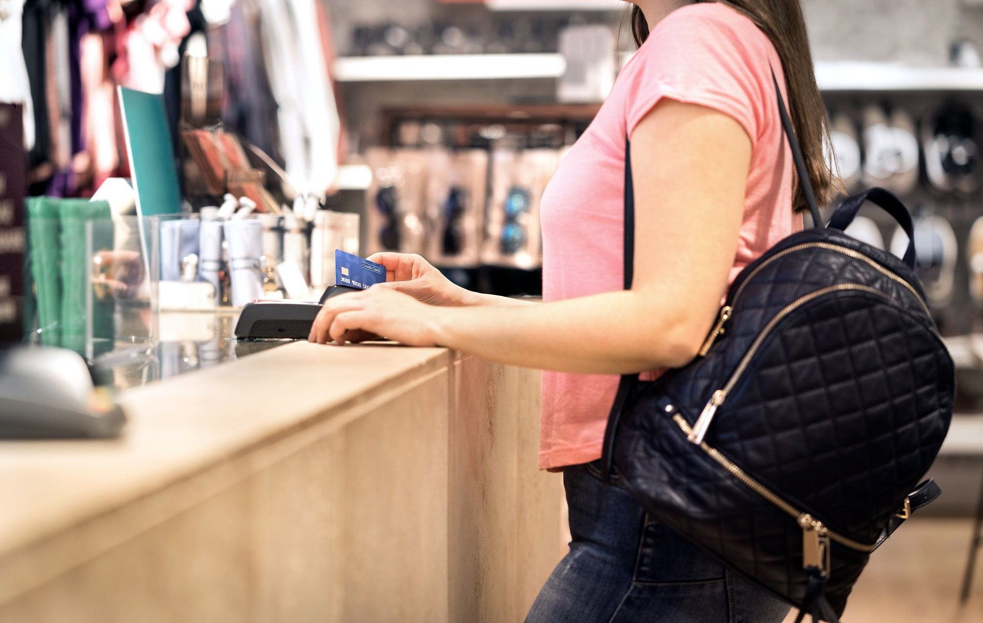 Woman at checkout in fashion store paying with credit card. Customer using payment terminal machine. Standing at counter. Buying and shopping for clothes. Bank card graphics are made up.
