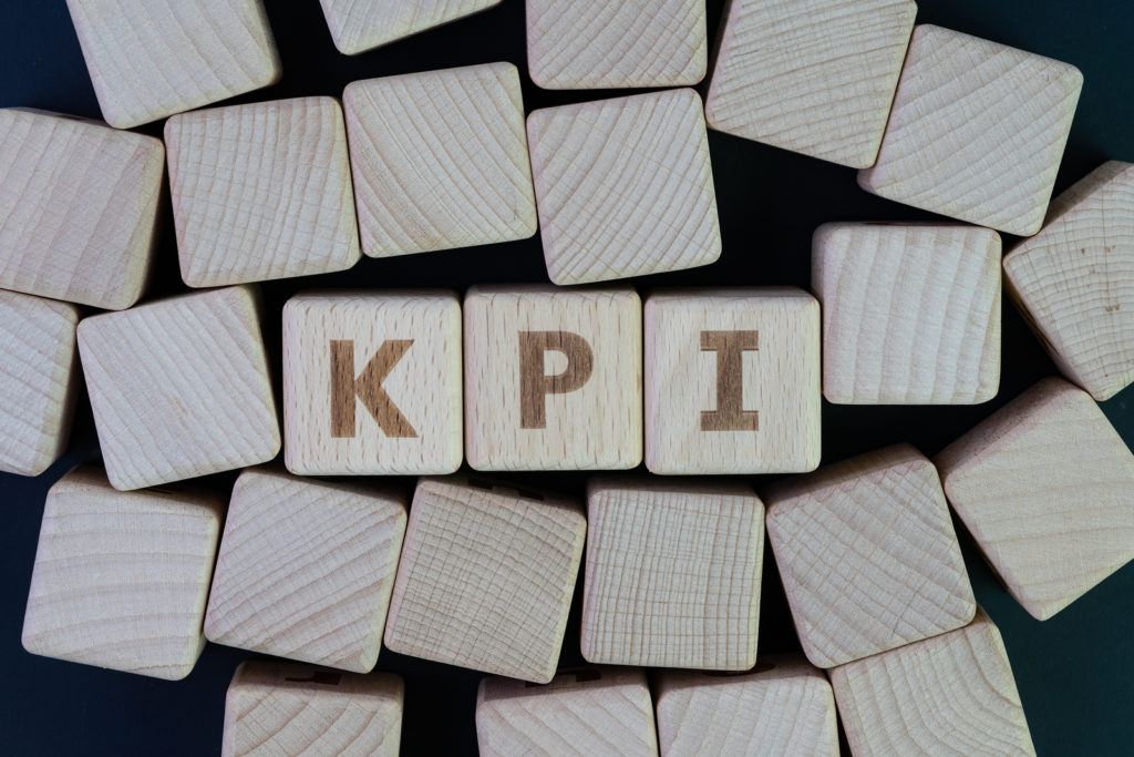 KPI, Key Performance Indicator wooden block letters on black background representing health food store retailers success