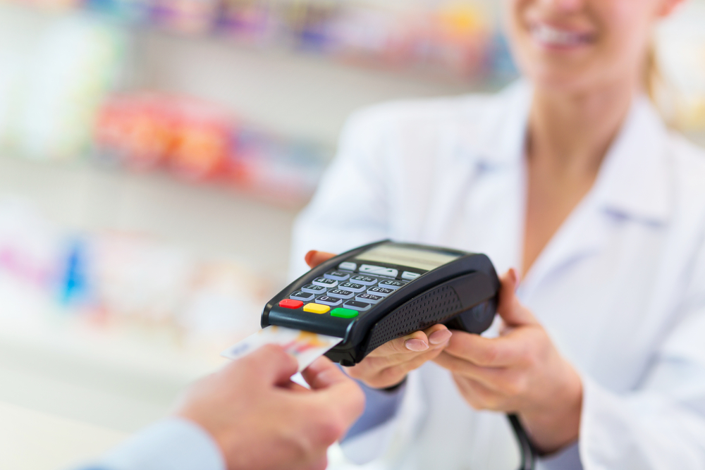 smiling female pharmacist accepting credit card payment from a retail pharmacy patient in a secure and safe way