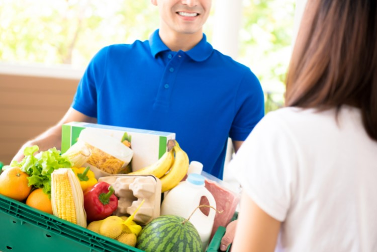 Grocery delivery service man in blue shirt delivers fresh groceries to woman at home