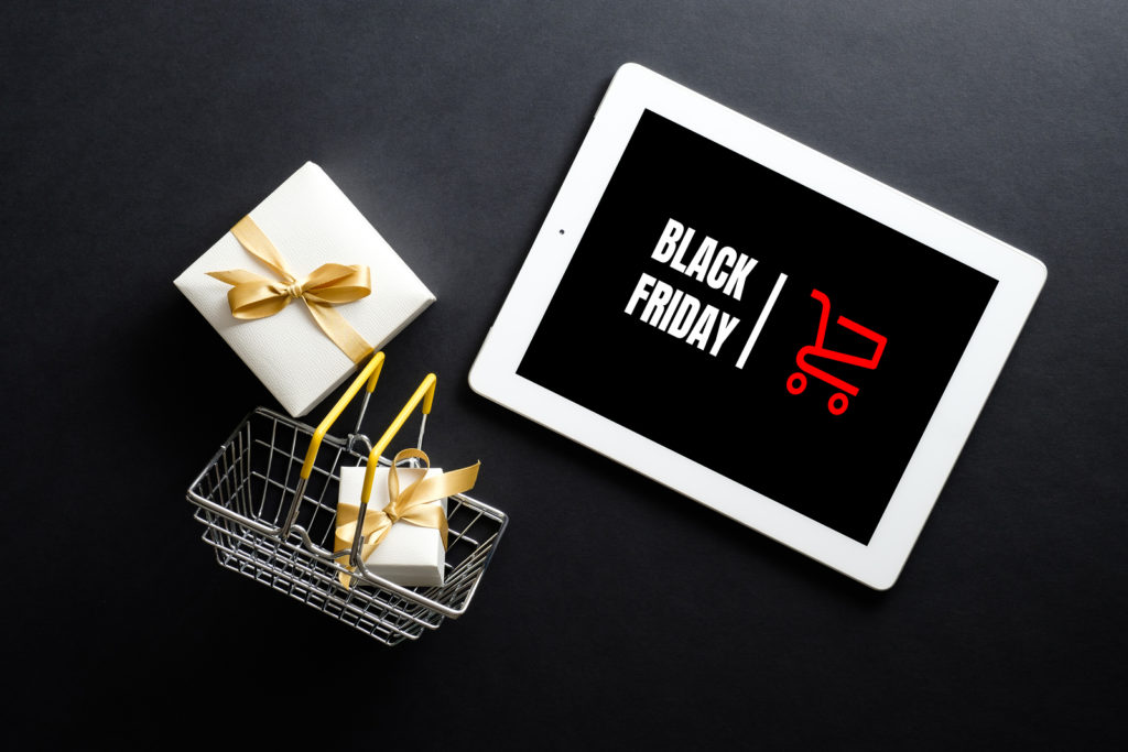Black Friday text on ipad screen with shopping basket and wrapped gifts to convey the message of how retailers can prepare for Black Friday