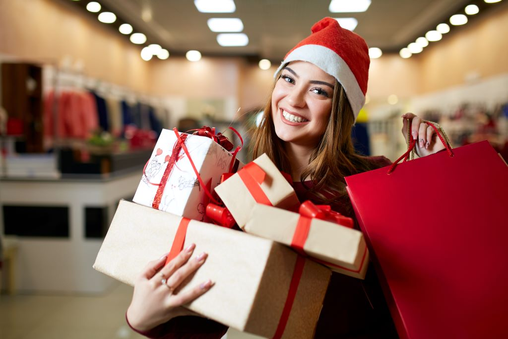 Female holiday shopper smiles holding her purchased gifts