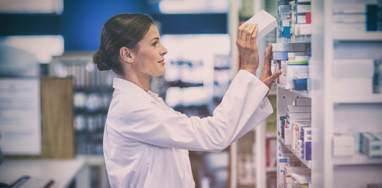 Female pharmacist selects medication to fill a pharmacy delivery order