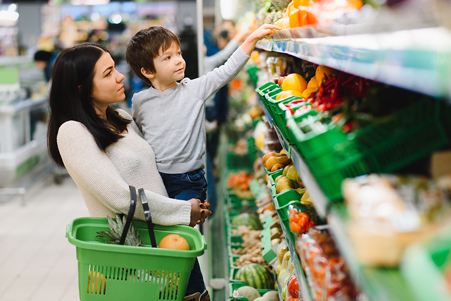 Young mother with her son at the supermarket.