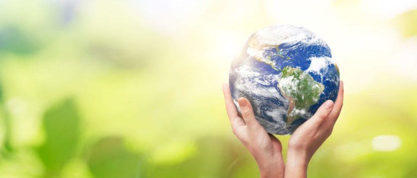 Hands cradling Earth against a green background