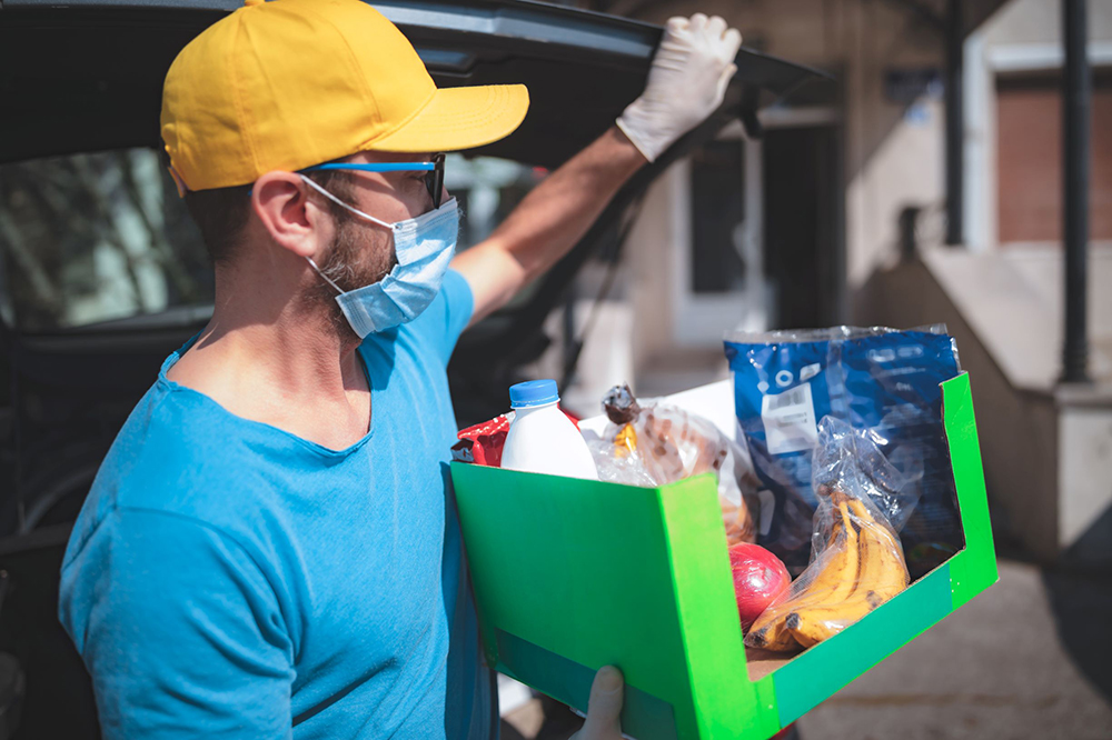Young man wearing mask unloads box of grocery delivery from vehicle