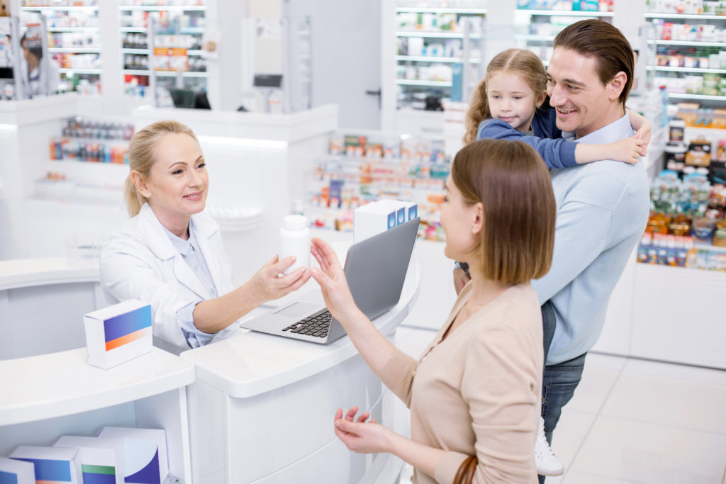 Family cashes with friendly female pharmacist out a their clinical pharmacy