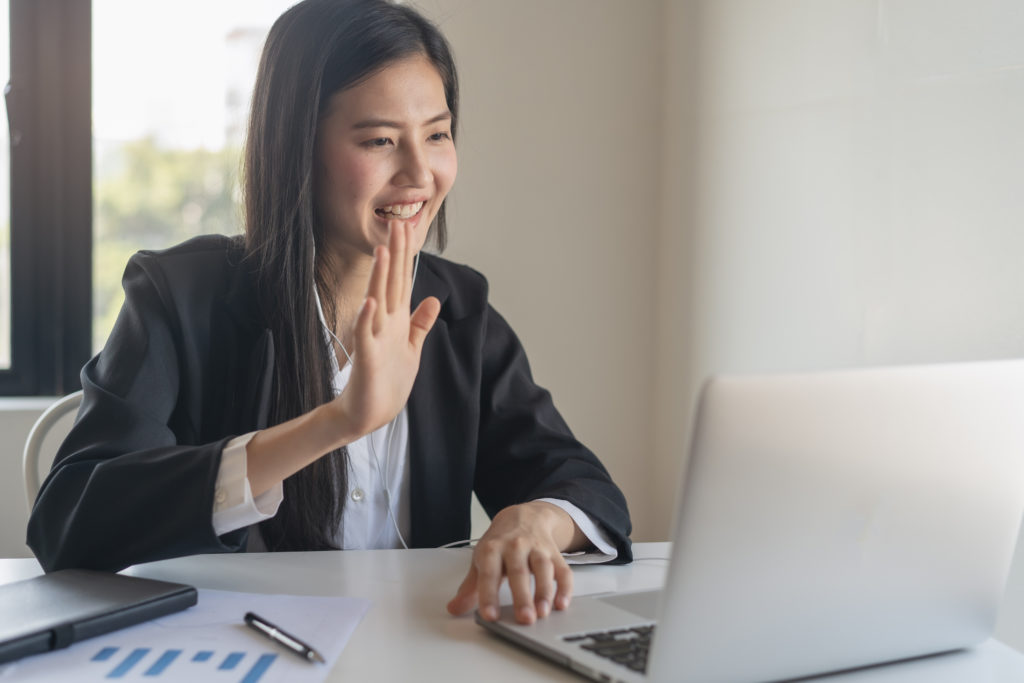 Business woman waves to client on a video conference meeting