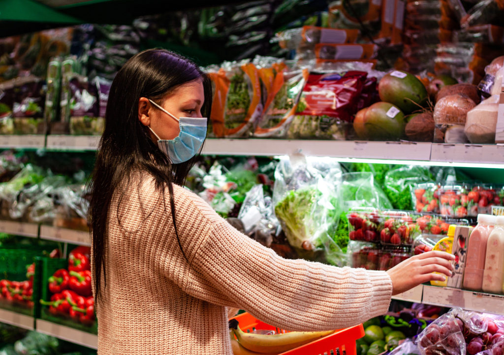 Woman in mask grocery shopping