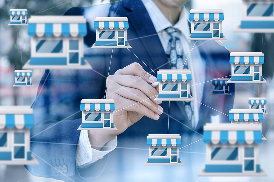 business man drawing a web between store icons with a blurred background