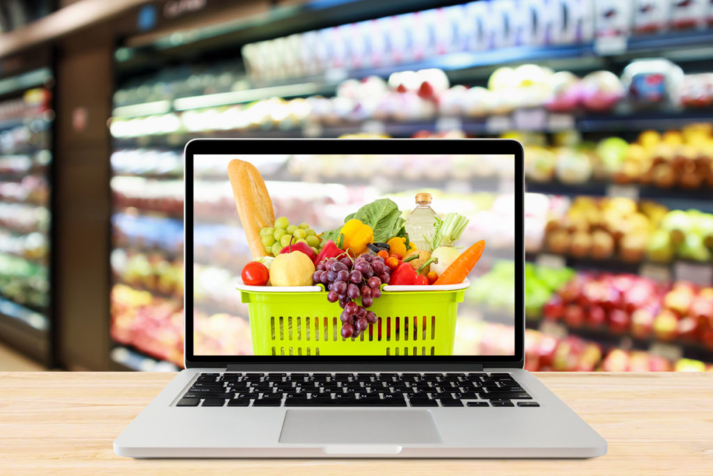 in a grocery aisle, a laptop showing groceries on its screen