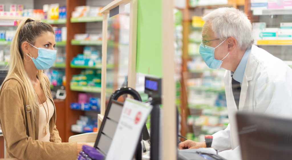 Masked woman checking out in a pharmacy,